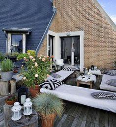 aménagement terrasse en bois composite avec des bancs et tables basses, coussins en noir et blanc et plantes en pots