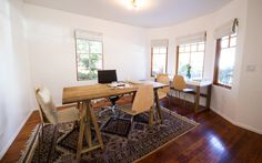 White walls, clean wooden furniture and bohemian rugs give this meeting space a decidedly unique feel. Plenty of large windows provides natural light and beautiful hardwood floors make for a warm, sunny space. Unique Furniture, Wooden Furniture, Wellness Studio, Hardwood Floors, Flooring, Coworking Space, Industrial Chic, Large Windows, Bohemian Decor