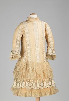 """c1885: American, silk: Length at CB 31.5"""". This is a very typical girl's party dress for the period. Alternating stripes of sheer material were prominent in both women's and girl's dresses. Made with much thought, seen in the double ruffles of the underdress sleeves, the overdress sleeves, the multiple ruffles of the skirt, and the underskirt. The low bustle effect in back and the long-waisted silhouette are appropriate for a young girl. The interior ties of the skirt create the bustle…"""