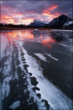 There is a firey sunrise behind Banff's famous Rundle Mountain, viewed from the Vermilion Lakes, Banff National Park, Canada.