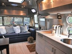 This luxe 25-foot Airstream International was decked out by Courtney Trent of Good Cottage, which rents out trailers for New York actors and directors to use on set. She removed the old sofa and installed a new one the width of a single bed and eight feet long, creating comfortable seating that can also be used for sleeping. A succulent garden is just inside the window behind the sofa, covering a bulky electronic box. See more at Courtney's Good Cottage.