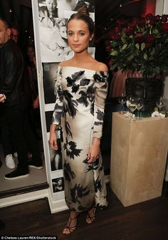 Elegance: Alicia Vikander exuded elegance in a creamy satiny gown with black flower design...