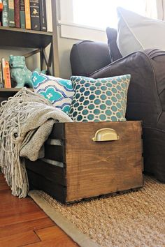 Finished DIY wooden storage crate with pillows and blankets inside. Great idea for pillows not in use!