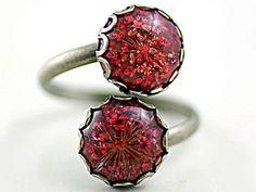 Ring mit 2 echten Blüten - rot. Bronzefarbener Ring mit 2 echten Blütensteinen von der wilden Möhre, eingegossen in rotbraunem Glasharz.   Der Ring lässt sich vorne in der Größe verstellen, indem man die Blütensteine auseinanderzieht bzw. zusammendrückt. Auf der Rückseite ist die Ringschiene so durchlaufend möglich. Auch in schwarz bei uns im Shop erhältlich.