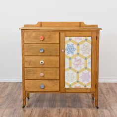This antique child's dresser is featured in a solid wood with a distressed light maple finish and eclectic drawer pulls. This small kids' armoire is in great condition with 5 drawers, a large interior cabinet and colorful removable quilt front. Perfect chest of drawers for a nursery or craft room! #eclectic #dressers #shortdresser #sandiegovintage #vintagefurniture