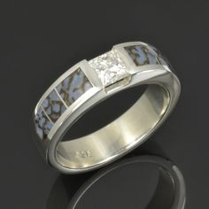 Men's fossilized dinosaur bone ring featuring a sparkling princess cut Moissanite set in sterling silver by Hileman Silver Jewelry. This blue dinosaur bone ring would make a great wedding band for the guy who is searching for something unique and unusual for is finger! #dinosaurbonering #uniquerings Dinosaur Bone Ring, Dinosaur Bones, Silver Jewelry, Sterling Silver Rings, Moissanite, Silver Casting, Thing 1, Wedding Bands, Princess Cut