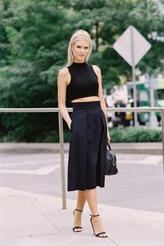 Black crop top worn with a black midi skirt and black ankle strap heels