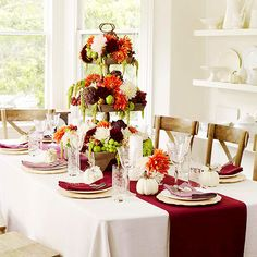 Use Contrast Colors and Scale A simple white tablecloth sets the stage for a dramatic, three-tiered fruit and flower arrangement. The combination of lime with burgundy, orange, and white is a gorgeous twist on classic fall colors. Draw eyes to the centerpiece with a bold table runner.