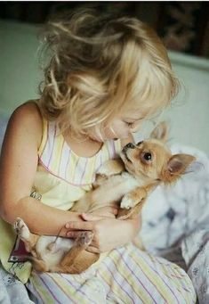 Little one holding a little pup. So sweet