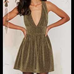 #113 You just struck gold. This dress features a gold lurex exterior, v-neck, straight waistband, slightly ruffled skirt, looped strap with cutout at back, and enclosed zipper. Fully lined. Pair it with an oversized velvet blazer and strappy black heels. By Nasty Gal. Nasty Gal Dresses Mini