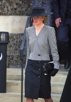 Princess Diana attends the memorial service in London for the victims of the Marchioness disaster. Diana is wearing a black & white check woolen coat dress by Catherine Walker & a plain black hat by Philip Somerville.