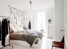 Feminine bedroom with single feature wall of wallpaper
