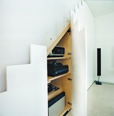 """In keeping with the maxim """"a place for everything and everything in its place,""""  any A/V equipment that does not need to be on show is hidden away in these neat push-to-open cupboards beneath the stairs. This means that you'd never spy  an unsightly trail"""