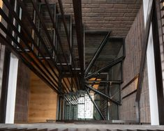 A blackened steel and glass staircase runs down the core of the house underneath a skylight and timber chandelier. London Townhouse, London House, British Architecture, Amazing Architecture, House Staircase, Stairs, Staircases, London Brick, Glass Structure