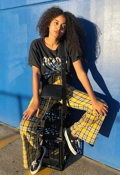 Yellow Clueless-style tartan pants are the perfect centerpiece and make for an edgy match paired with a tied-up band tee. And for that all-day stamina, low-top skate-vibes Converse and a simple leather cross-body.