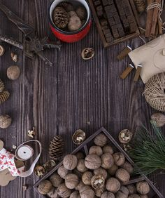 Christmas wooden background with gift, fir-tree, Walnut, pine cones. by Oksana Ariskina on Creative Market
