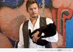 Norman Reedus aka Daryl Dixon - Norman Reedus who plays Daryl Dixon in The Walking Dead posing holding a black cat. He also played Murphy MacManus in The Boondock Saints.