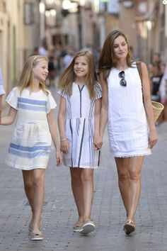 Queen Letizia of Spain (R) and her daughters Princess Leonor (L) and Princess Sofia, pose as they walk down a street in the village of Soller on Mallorca island, on August 6, 2017