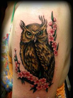Horned Owl Sitting On Blossom Branch Tattoo On Biceps