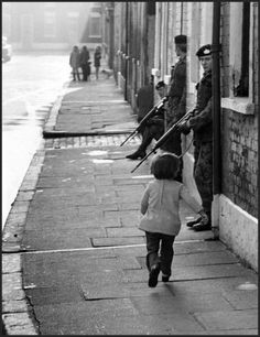 Young girl skips past patrolling British soldiers from the Gloucester Regiment, Belfast, Northern Ireland, 1972 by Oliver Morris/Getty