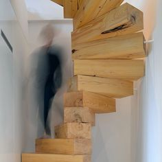 A spiralling stack of chunky wooden blocks forms this staircase designed by architecture studio QC for an apartment in Poland.