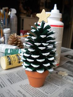 "Pinecone Christmas Tree.  Simply, paint the pine cone with green paint and let it dry. Apply some regular glue on the edge of each spine on the pine cone and sprinkle some glitter. Once it's dry, hot glue the pine cone to the terra cotta pot and glue the star on top.I painted white on the tips of the ""pedals"" of the pine cone to give a ""snow"" effect."