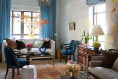 Smaller furniture pieces, such as vintage scroll-arm chairs and a ceramic garden stool, are easily moved about the living area to best suit the occasion and number of guests. Deep teal velvet upholstery complements the rusty coral tones of a Pasargad Turkish rug.