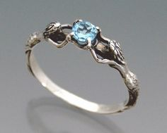 Delicate and subtle, two lovely mermaids present a 4mm aquamarine in sterling silver. (Swiss blue topaz pictured)  I have heard the mermaids singing, each to each. ~ T.S. Eliot  ***PLEASE NOTE: Due to the volume that we receive in requests for this ring, please ALLOW AT LEAST 2 WEEKS LEAD TIME for special delivery dates to be fulfilled. ***  Ring sizes are subject to availability at time of order.  We will make your ring to order, so you may include 1/4 size or 1/2 size if that is what size…