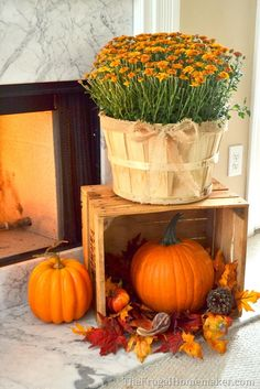 Fall mums and pumpkins give this fireplace a lovely, warm look for autumn. See more simple fall decorating ideas on The Frugal Homemaker. || @frugalhomemaker