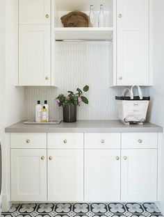 In this laundry room, matte gold knobs dress up plain white cabinets.   Photographer: Travis J Photography   Designer:Studio McGee
