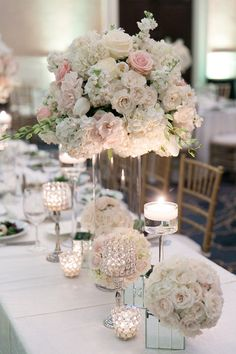 Elegant, romantic and classic wedding centerpieces - pastel pink roses + white lisianthus and hydrangeas in clear glass vessels + votive candles {Arte De Vie}