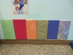 This is a sensory wall I created in my infant/young toddler classroom. I wrapped pieces of cardboard in a variety of textures. The ones I used were felt, tin foil, contact paper, bubble wrap, burlap, and the plastic they wrap couches in. I simply taped the material to the cardboard with masking tape and then taped them to the wall. It is a great way for the infants to experience textures.