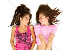teenager looking at each other and smiling. - Teenagers looking at each other and smiling against white background.
