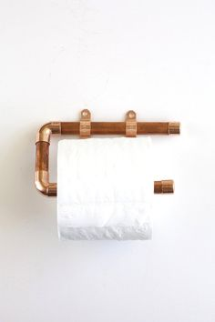 DIY wood and copper toilet paper holder hung on white wall