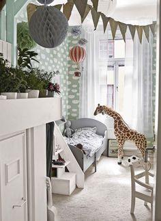 Barnrum med pasellgröna väggar. Giraff, mjukdjur.