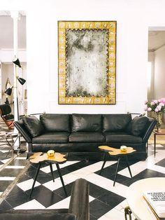 Sofá preto e mesinhas orgânicas