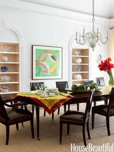 In this dining room, a plaster-dipped chandelier and niches lined in Twenty2's Paperweave lighten the look of the 18th-century table.