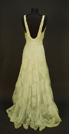 """Back View of WORTH NET EVENING GOWN with SEASHELL DESIGN, c. 1932. Sleeveless pale seafoam green V-neck decorated with large shells of various types, the straps with iridescent sequin decoration and scattered rhinestones at shoulder and down low back, attached seafoam crepe de chine slip, side closure. Label """"Worth"""". Belonged to Elizabeth Arden, purchased from employee who received dress as a bequest at Arden's death. Bust 34, waist 25, length 61."""