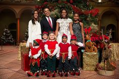 """President Barack Obama, First Lady Michelle Obama, and daughters Malia and Sasha join young """"elves"""" for a photo prior to the """"Christmas in Washington"""" taping at the National Building Museum in Washington, D.C., Dec. 15, 2013. (Official White House Photo by Pete Souza)"""