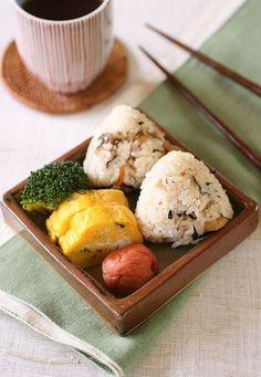 rice ball of takikomi-gohan (a rice dish seasoned with soy sauce and boiled with various ingredients), tamagoyaki (Japanese omelette), umeboshi (pickled ume), broccoli ingredients of takikomi-gohan : rice, carrot, burdock, lotus root, hijiki, chicken, konnyaku, fried bean curd, sake, mirin, lightly flavored soy sauce, salt
