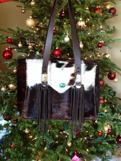 A custom order Buckaroo Diaper Bag. Lined with large interior pockets for diapers and baby wipes, a sleeve for a baby bottle and a key clip. Hair on hide exterior and suede fringe . Made to order by gowestdesigns.us