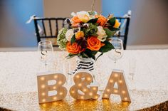 Black White and Gold Wedding Reception Bride and Groom Table with Block Letter Initial Signs and Tropical Orange and Greenery Bouquet