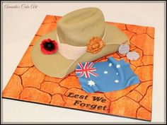 Anzac day cake featuring slouch hat, Australian flag, dog tags and poppy on cracked red earth board by Amanda's Cake Art