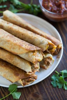 Crispy Bean and Cheese Burritos are guaranteed to be family approved, and perfect for an easy weeknight meal. They include seasoned refried beans and fresh shredded cheese layered inside a tortilla and cooked until crispy. Refried Bean Burrito, Bean And Cheese Burrito, Bean Burritos, Mexican Burritos, Bean And Cheese Enchiladas, Mexican Dishes, Mexican Food Recipes, Vegetarian Recipes, Dinner Recipes
