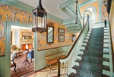American version of a Georgian interior: In the main hall, wood floors are marbleized, the block print paper pattern dates to 1776, and the ca. 1880 Wilton stair carpet is a reproduction.
