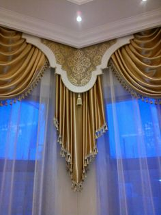 This beautiful bay window treatment includes a corner cornice with contrast banding, over swags and cascades, over sheers.  Design by?  Please let me know if this is your design.