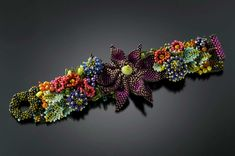 September Fiori Cuff - A beautiful arrangement of jewel tones flowers, featuring a plum dahlia,  sea holly and a variety of leaves. $550 http://www.juliepowelldesigns.com/product/settembre-fiori-cuff-black-dahlia/