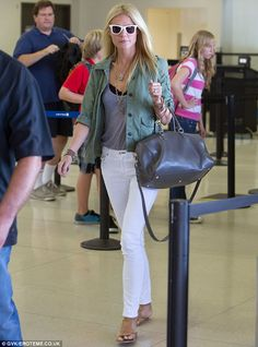 Airport chic: Paltrow looked causal in a khaki shirt, white jeans and tan sandals. Love her mala bead bracelet and the beltless look {Brit trend}