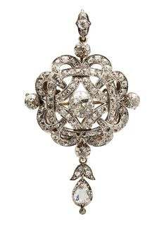 A late 19th century diamond set brooch/pendant, claw set with an old cushion cut diamond in an open scrolling mount, set throughout with old cut diamonds, suspending a detachable drop set with a pear shaped diamond and further small diamonds.