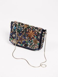 Sparkle and shine with this heavily embellished crossbody bag featuring…
